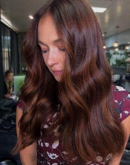 Faits saillants en cuivre: femme avec de longs cheveux de vin auburn foncé avec des reflets cuivrés doux au fini ondulé portant un haut à motif