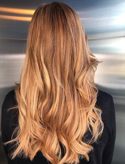 Faits saillants cuivrés: Vue arrière d'une femme aux longs cheveux ondulés blonds fraise avec des reflets