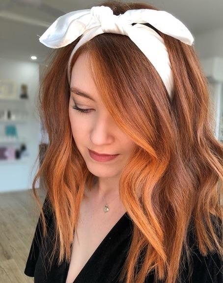 Faits saillants en cuivre: Femme aux cheveux mi-longs en cuivre bouclés avec des reflets encadrant le visage