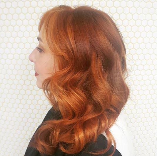 Faits saillants en cuivre: vue de côté d'une femme avec des cheveux ondulés de longueur moyenne en surbrillance de cuivre portant un haut foncé