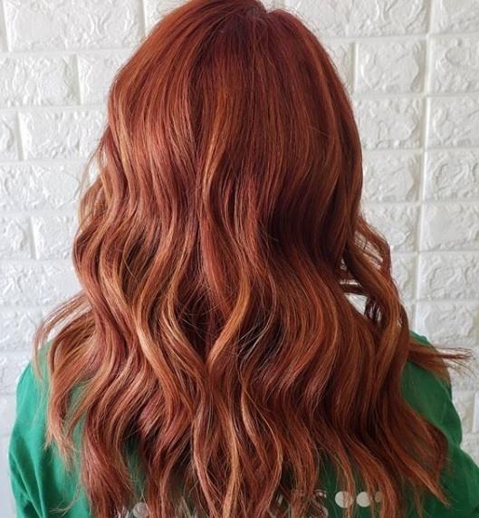 Faits saillants cuivrés: Vue arrière d'une rousse aux cheveux bouclés cuivrés, vêtue d'un haut vert