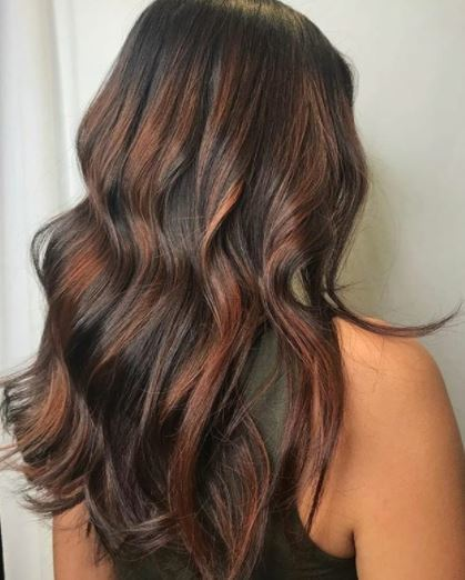 Faits saillants en cuivre: vue arrière d'une femme aux longs cheveux bruns ondulés avec des reflets cuivrés portant un gilet noir