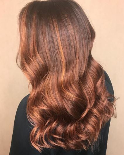 Faits saillants en cuivre: vue arrière d'une femme avec des reflets en or rose et en cuivre sur de longs cheveux ondulés portant un haut noir