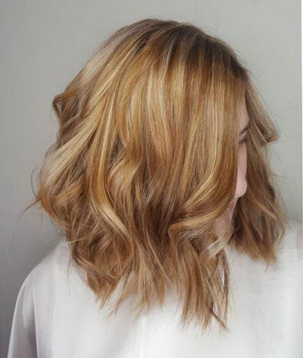 Faits saillants en cuivre: femme aux reflets cuivrés blonds et longs bob ondulés portant un haut blanc