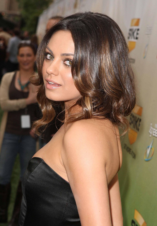 mila kunis avec balayage caramel cheveux bouclés de longueur moyenne portant une robe bustier en satin noir à la remise des prix