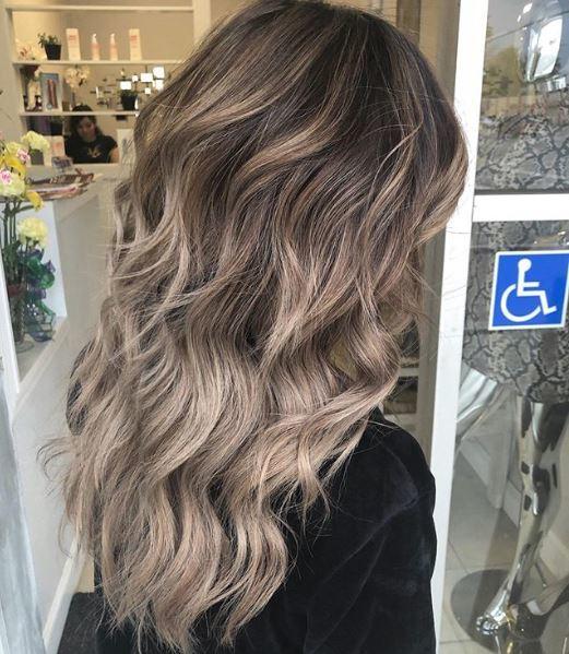 Femme aux longs cheveux bruns cendrés froids ondulés