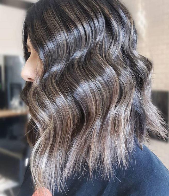 Femme aux cheveux ondulés brun cendré