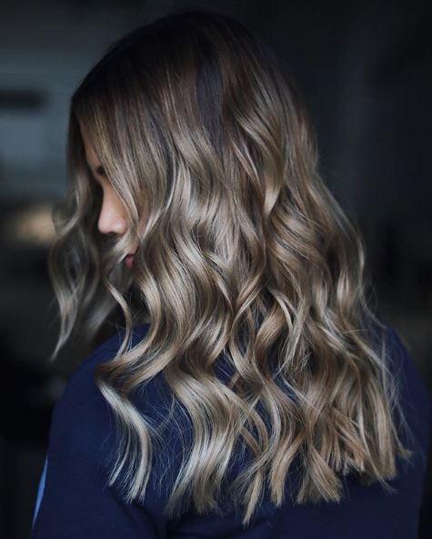 Femme aux longs cheveux bouclés brun cendré