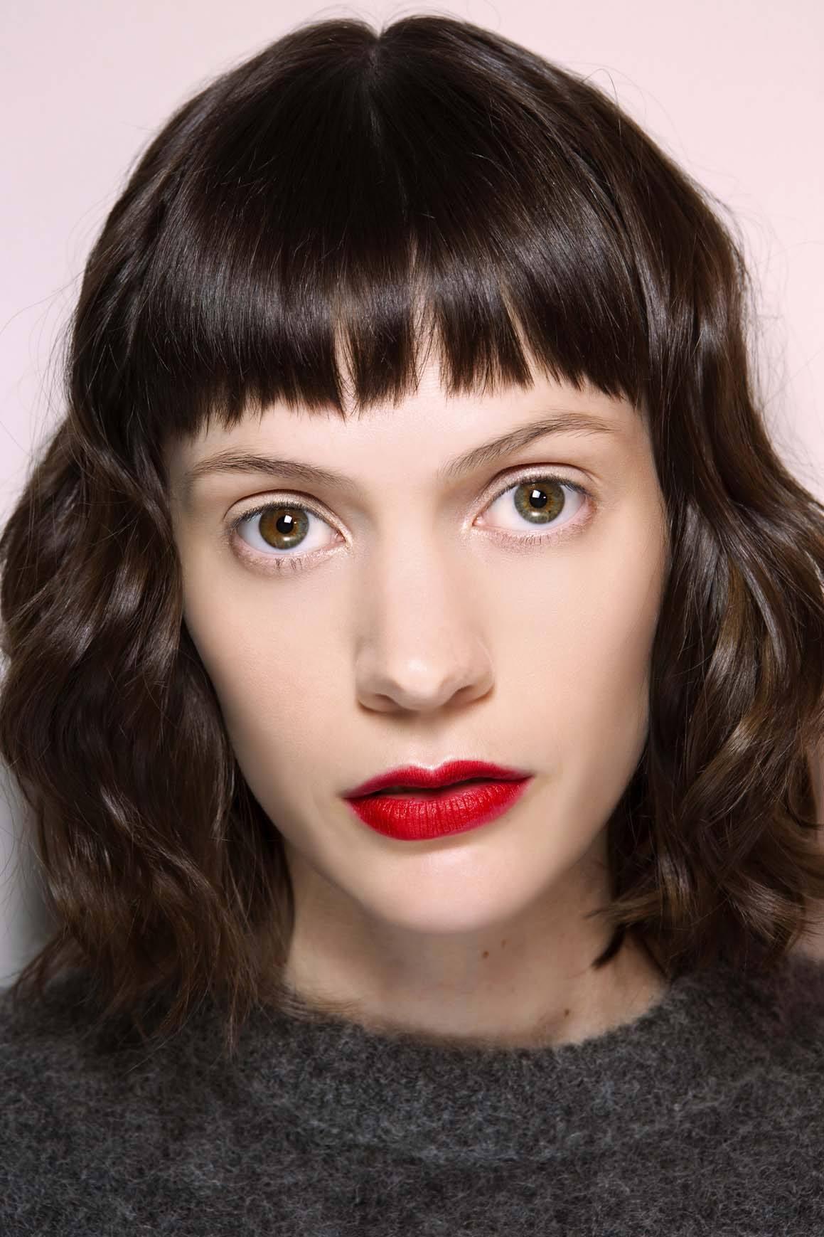 Frange courte: Femme aux cheveux ondulés marron foncé brillants avec micro frange et rouge à lèvres.