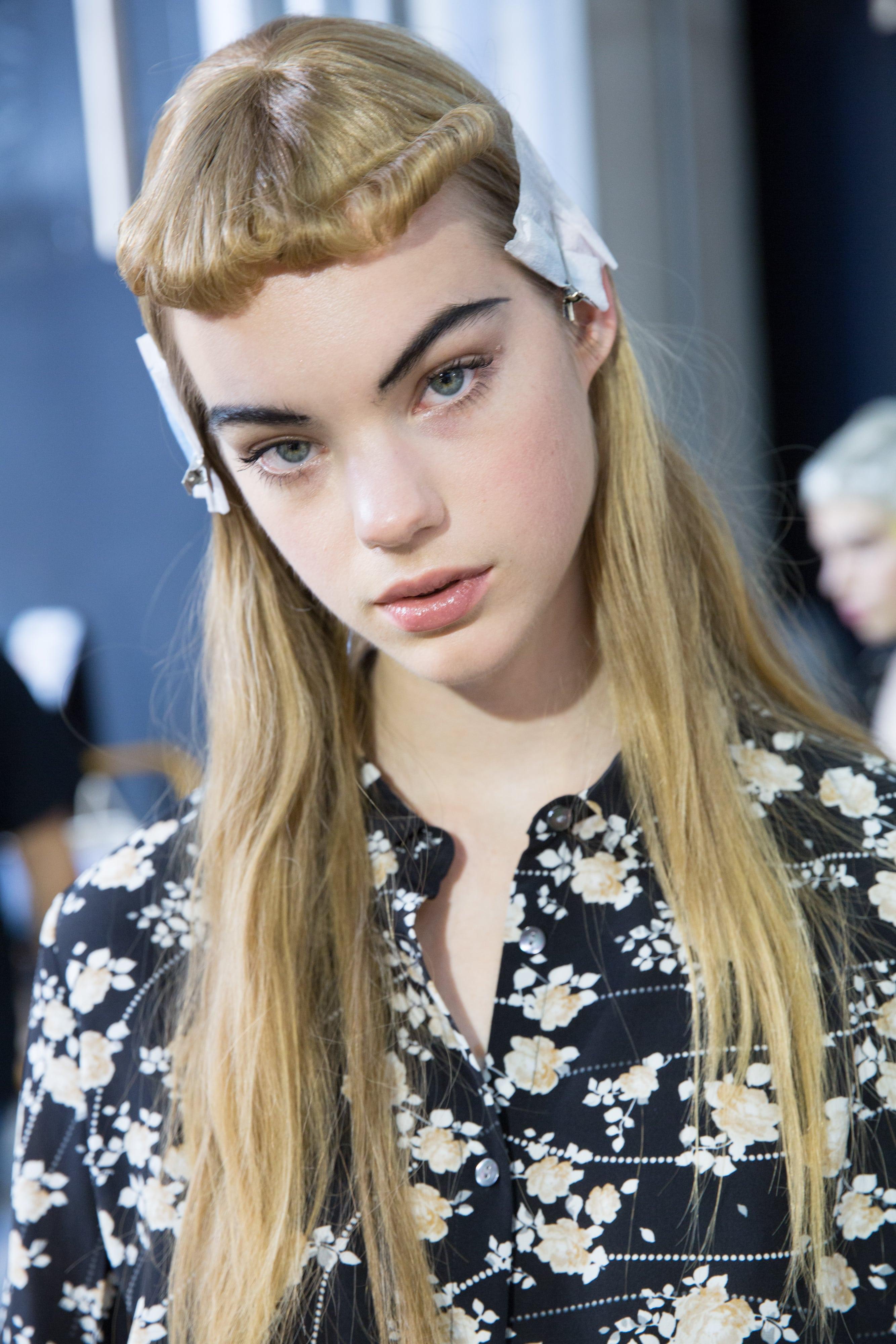 Frange courte: Modèle blonde aux cheveux longs et micro frange courte enroulée rétro dans les coulisses d'un défilé de mode.