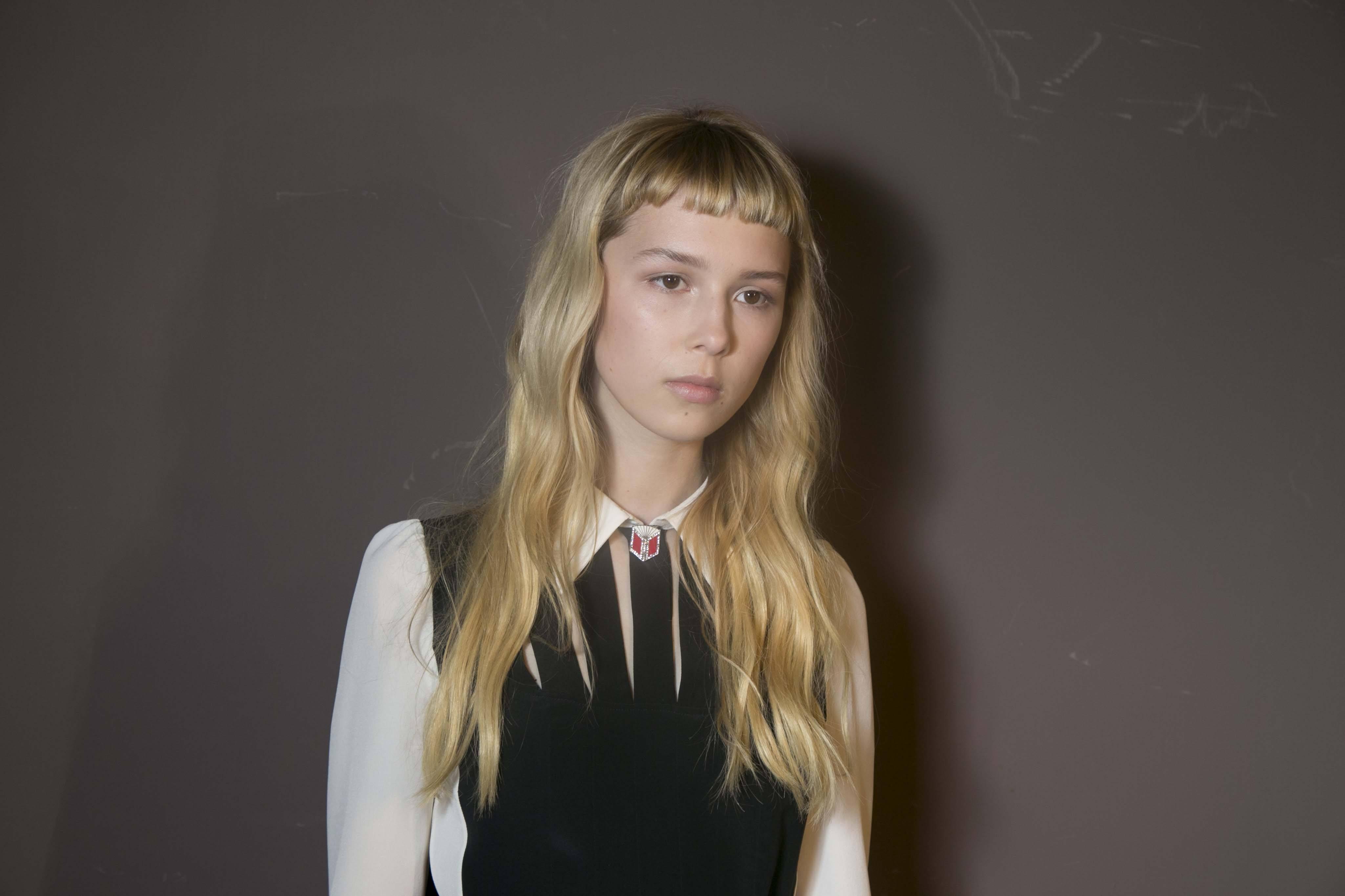 Frange courte: Femme aux longs cheveux blonds ondulés avec une micro frange courte portant une chemise blanche.