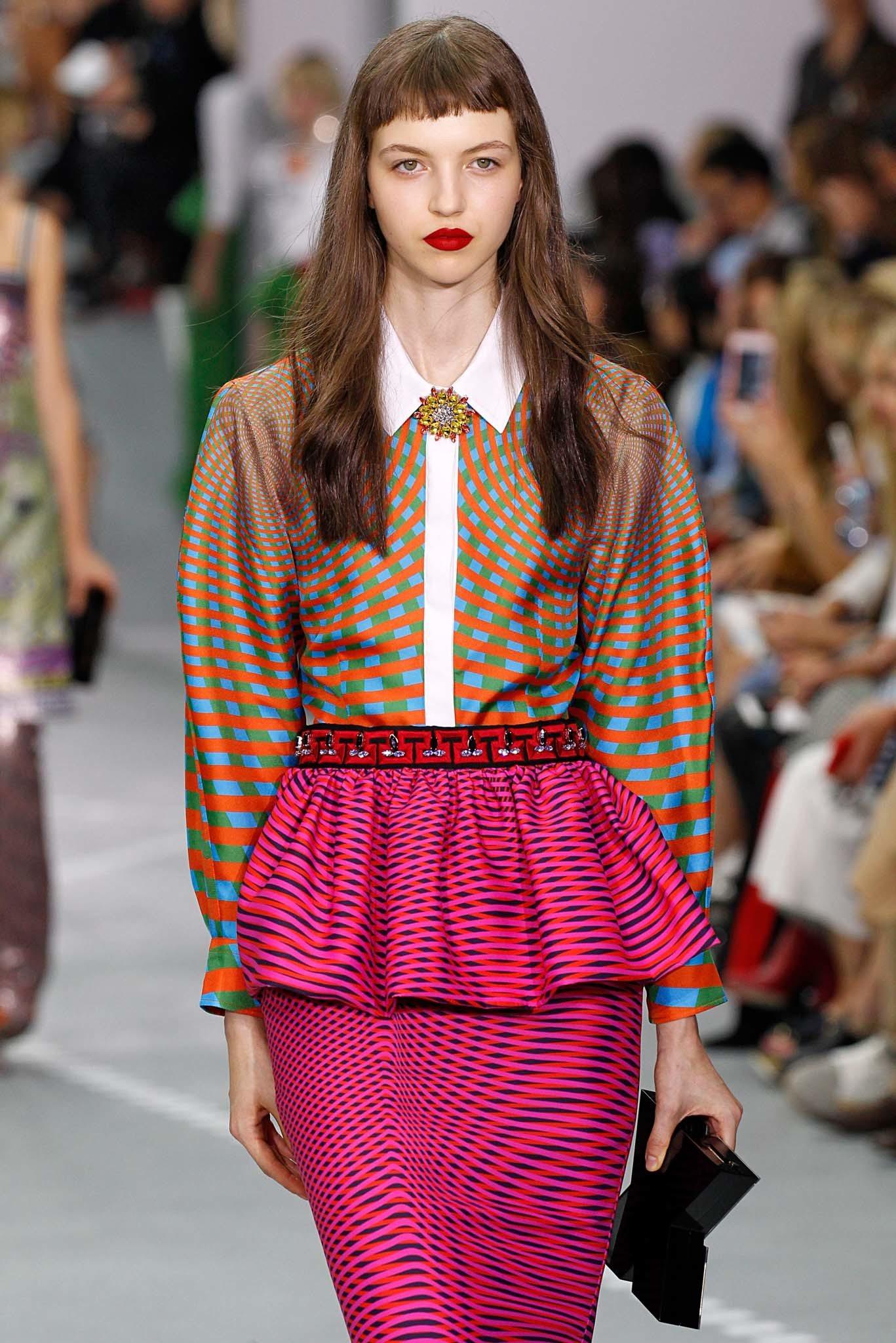 Frange courte: Modèle avec de longs cheveux bruns ondulés et une micro frange courte portant une chemise et une jupe à motifs.