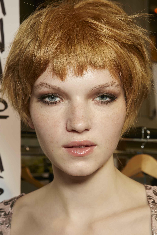 Frange courte: Modèle avec de courts cheveux blonds à la fraise agitée et une micro-frange.