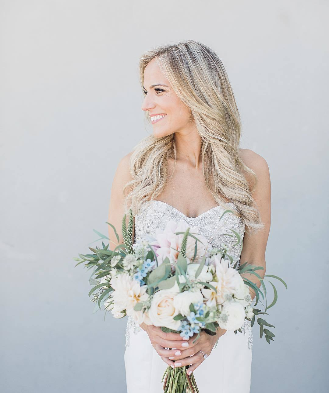 Classic wedding hairstyles: Woman with long bleach blonde hair styled into loose curls, wearing sweetheart wedding dress and holding flowers