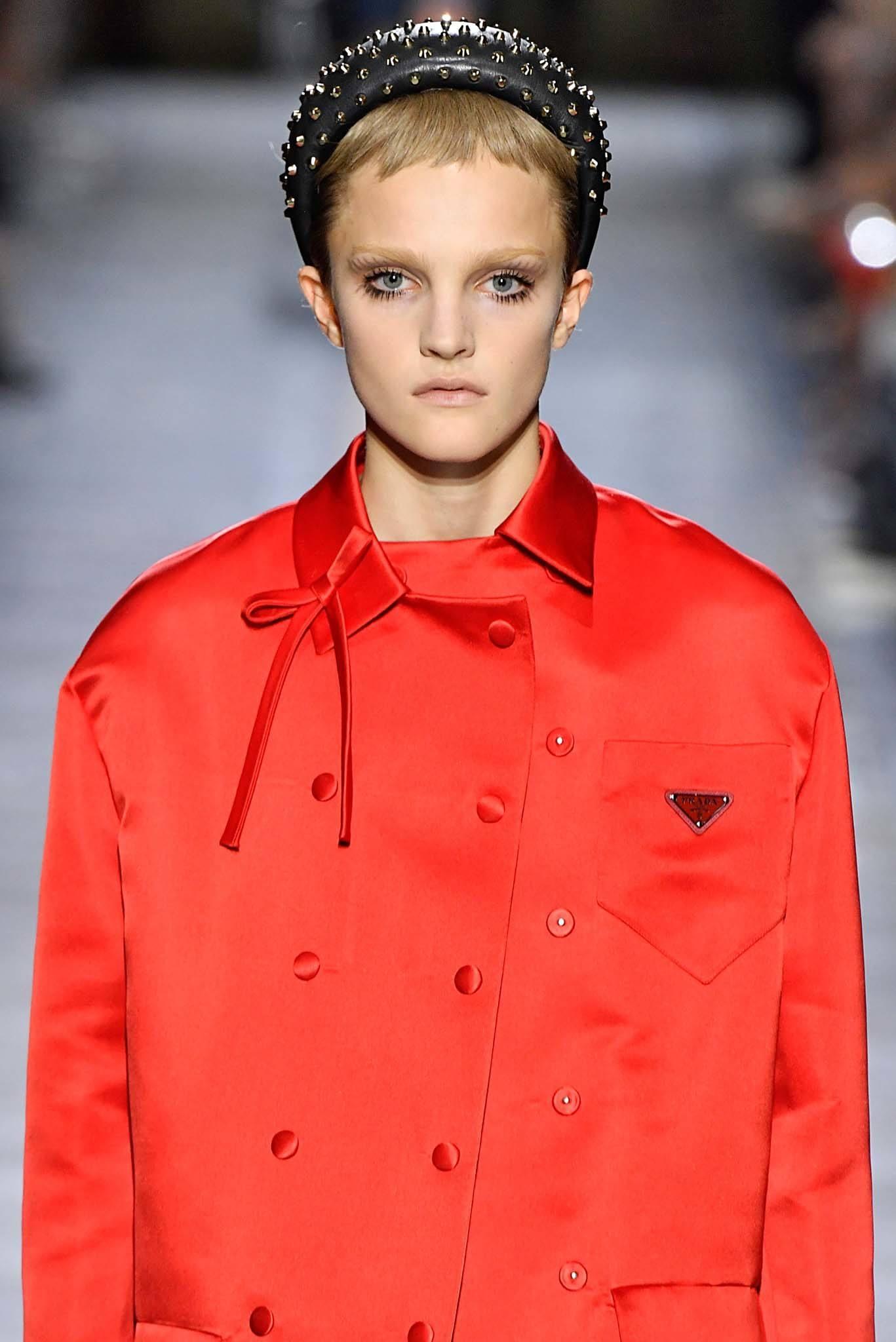 Frange courte: Modèle aux cheveux blonds portant un grand bandeau avec micro frange chez Prada.