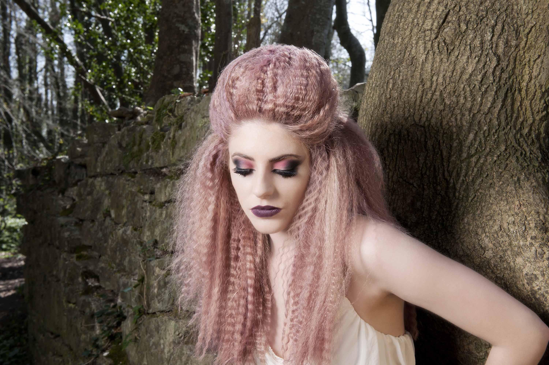 femme aux cheveux rose pastel frisés en demi-lune, appuyée contre un arbre