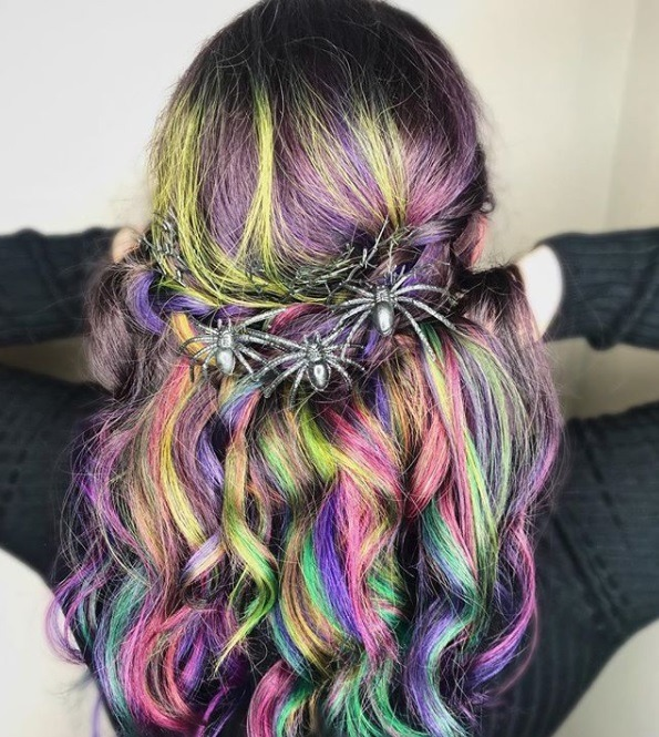 Coiffures d'Halloween : Plan arrière d'une femme aux longs cheveux colorés en vert, violet, rose et bleu, coiffée en une coiffure tressée à mi-hauteur, avec des accessoires de coiffure d'Halloween en forme d'araignée