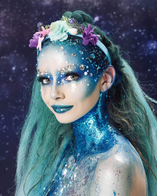 Coiffures d'Halloween : Femme habillée comme une sirène, avec de longs cheveux bleus, une tresse de licorne et un bandeau floral, portant du maquillage bleu et des paillettes bleues