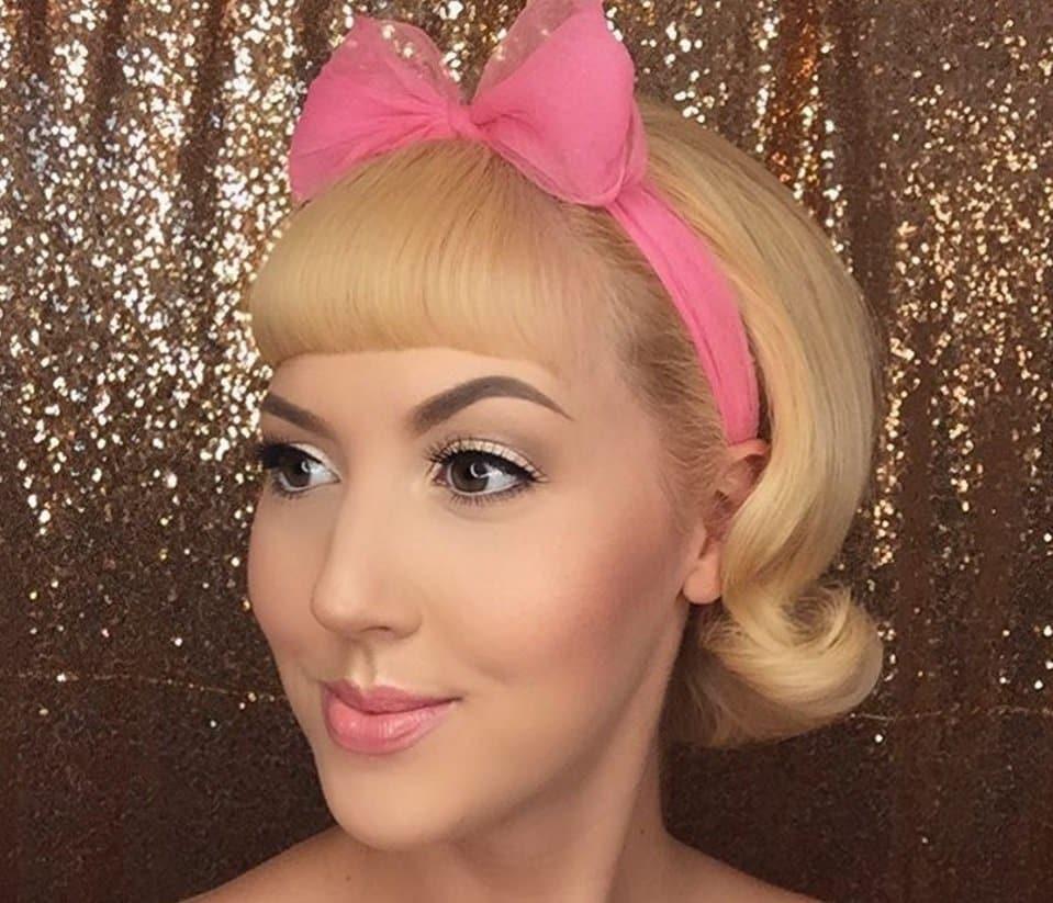 femme aux cheveux blonds courts dans un style bob rockabilly et une frange portant un nœud de cheveux roses