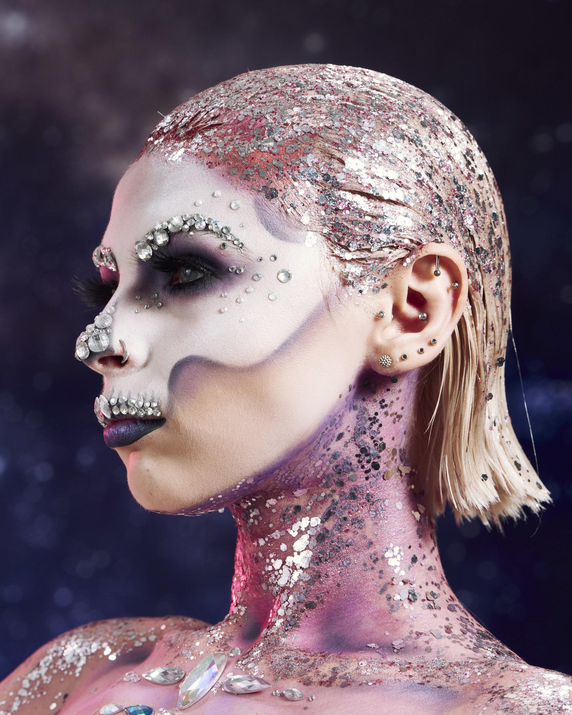 Coiffures d'Halloween : Femme maquillée avec un crâne en sucre, avec des cheveux blonds courts et des paillettes argentées dans le dos, ainsi que sur le cou, posant dans un studio