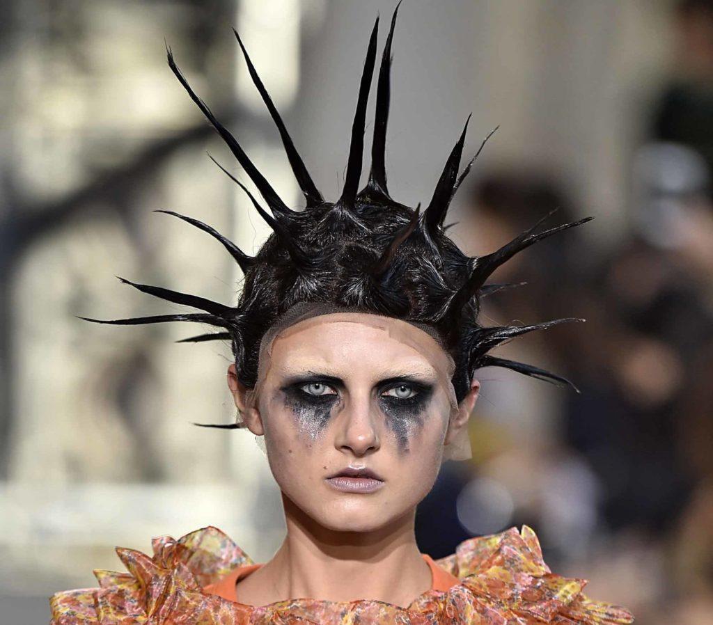 mannequin de défilé avec des cheveux noirs en longs pics et un maquillage taché