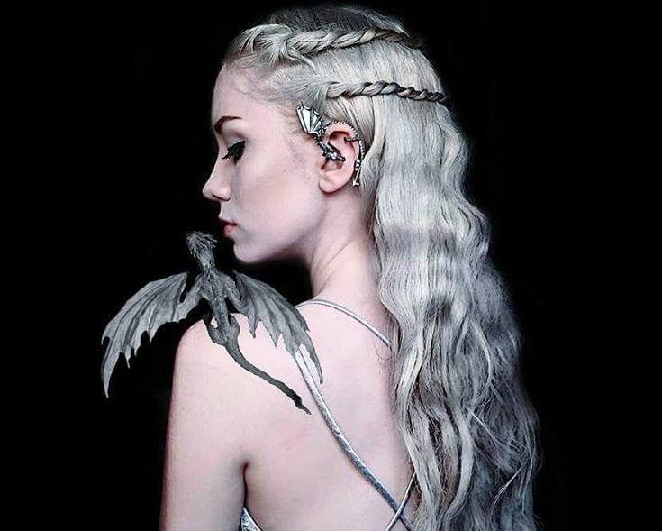 Coiffures d'Halloween : Femme habillée en Khaleesi de Game of Throne, avec ses longs cheveux blonds argentés coiffés en vagues lâches avec deux tresses, portant de l'argent et posant avec un dragon CGI sur son épaule