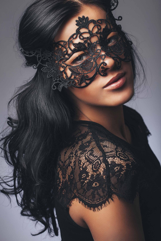 Coiffures d'Halloween : Femme aux longs cheveux noirs en vagues portant un masque de mascarade et un haut en dentelle noire