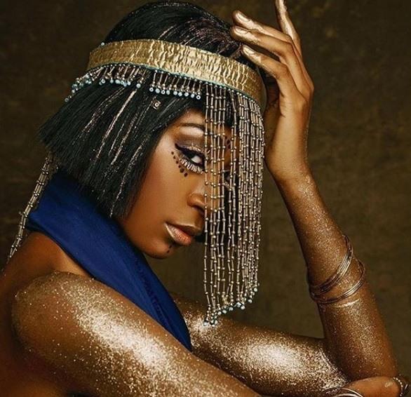 Coiffures noires d'Halloween : Femme habillée en Cléopâtre avec une courte coiffure noire en bob, portant une coiffe dorée avec une robe en soie bleue à paillettes dorées sur le corps