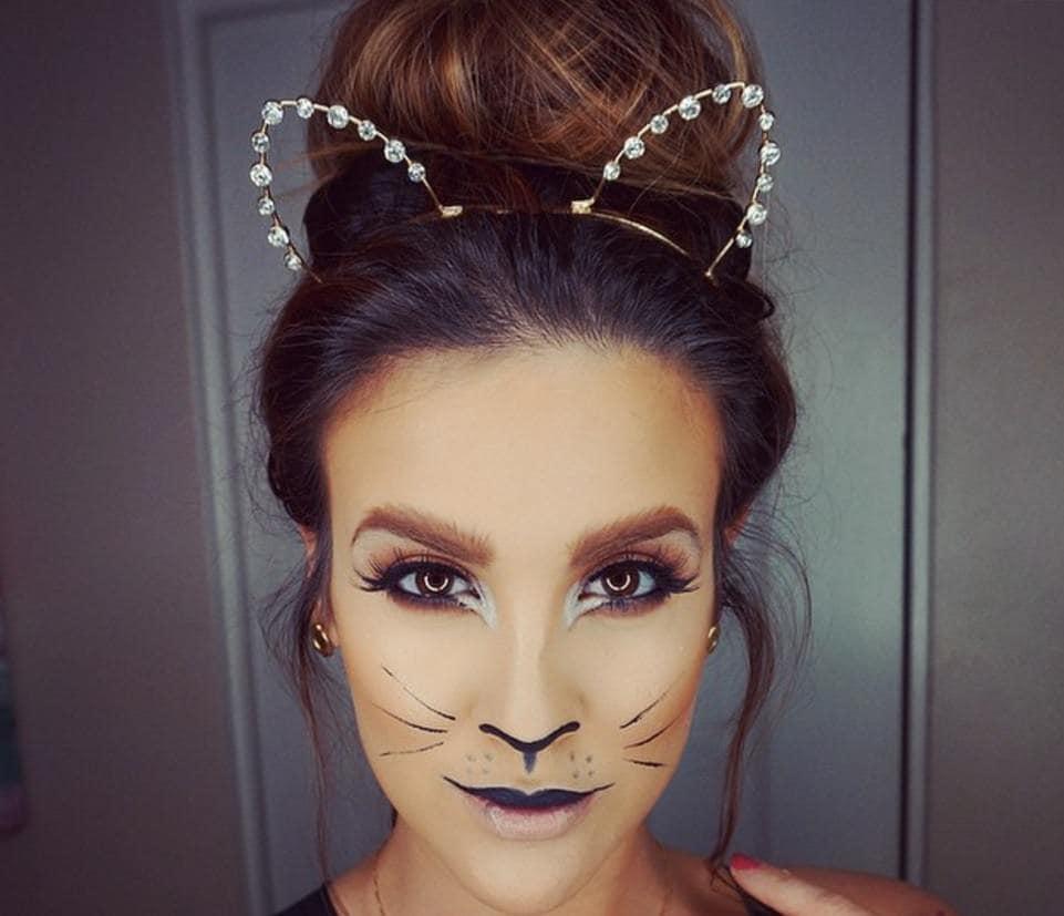 femme aux cheveux bruns dans un grand chignon avec un maquillage de chat et portant un bandeau pour les oreilles de chat