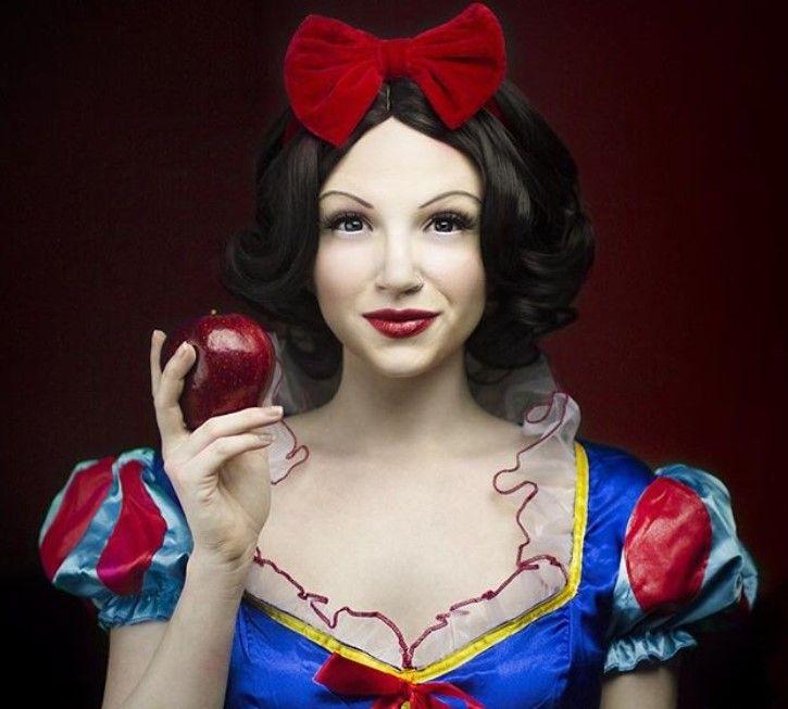 Coiffures d'Halloween : Femme habillée en Blanche-Neige, avec ses cheveux noirs courts coiffés en boucles avec un accessoire pour cheveux en noeud rouge, tenant une pomme et posant dans un décor de studio
