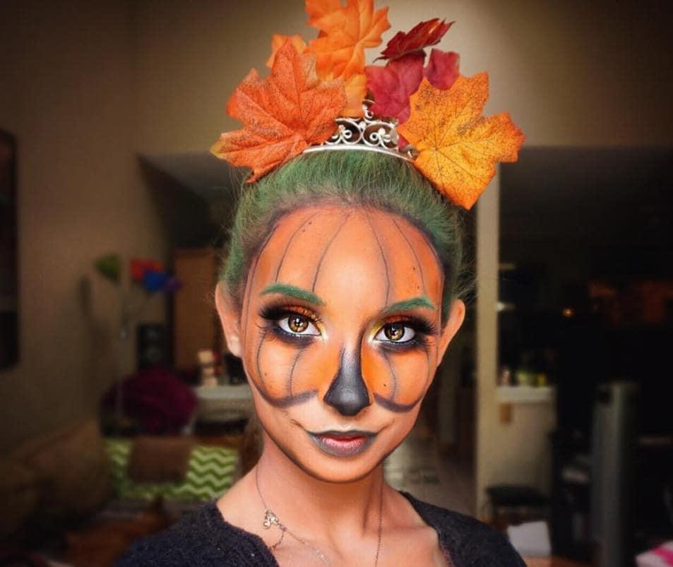 femme au visage peint en citrouille et aux cheveux verts avec des feuilles d'automne