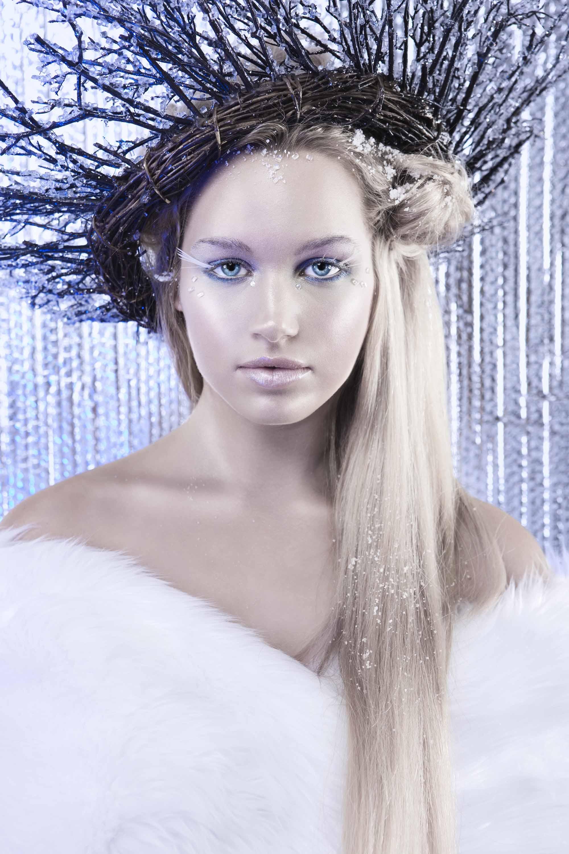 Coiffures d'Halloween : Femme habillée comme une reine de glace avec de longs cheveux blonds, portant une fourrure blanche et des brindilles dans ses cheveux