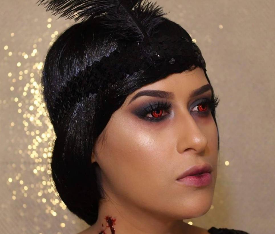 femme au look inspiré de celui d'une fille à clapet, avec un bandeau de plumes et des yeux rouges