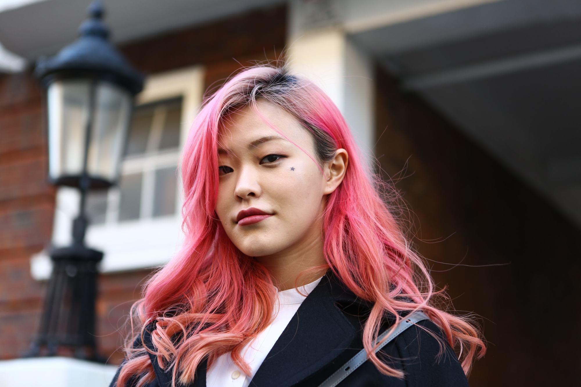 Fille asiatique aux cheveux roses teints se tenant à l'extérieur