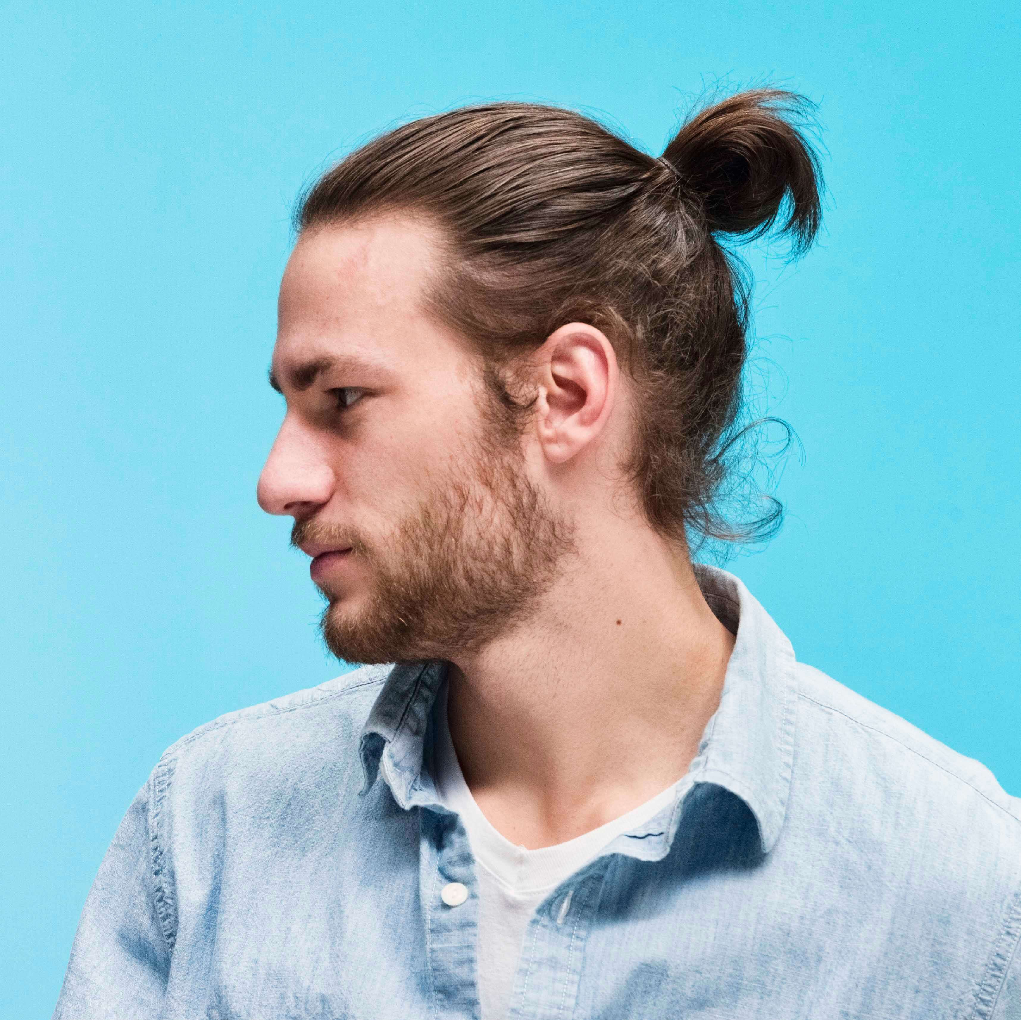 Un homme aux cheveux bruns dans un chignon