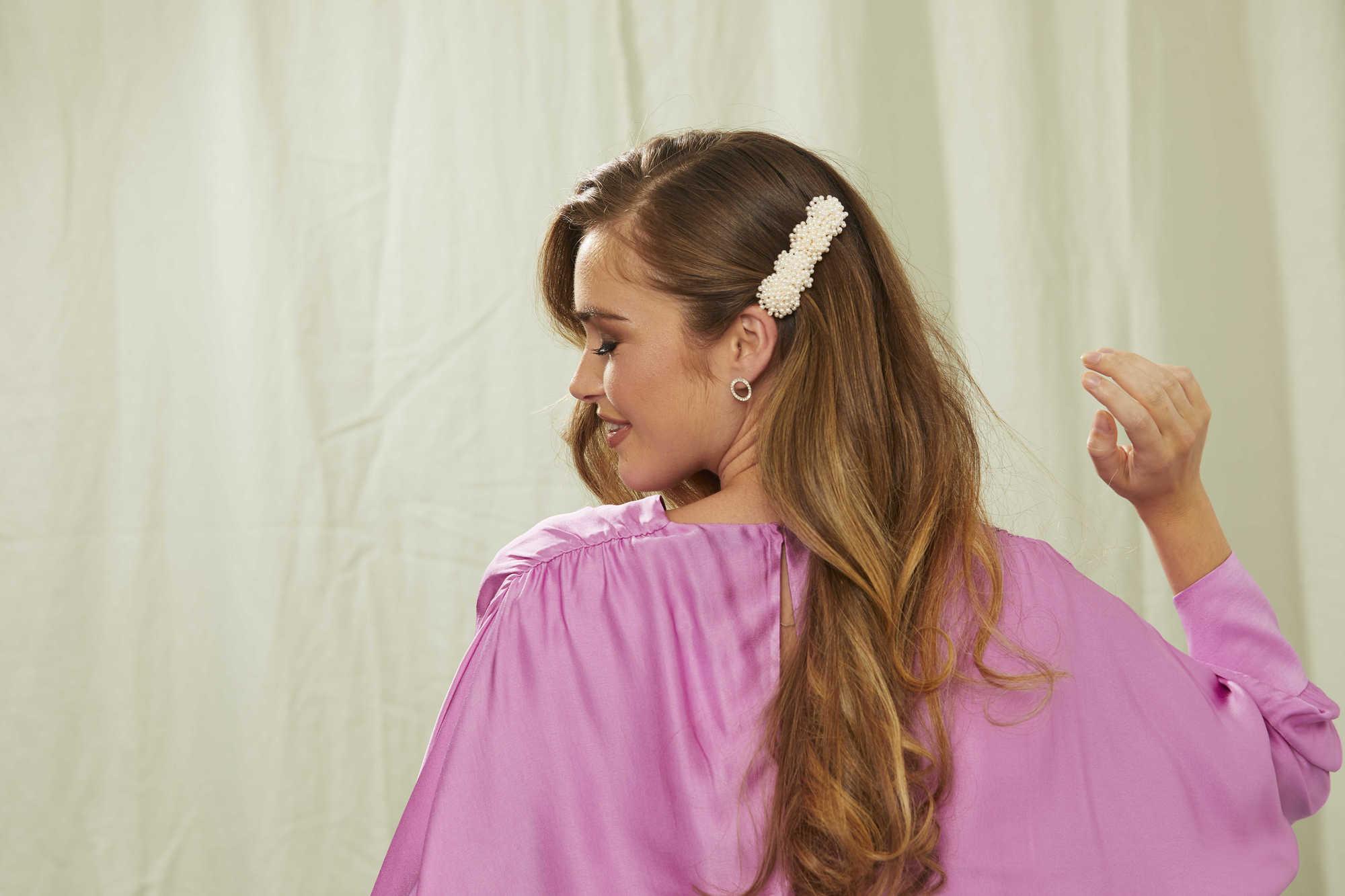 Femme aux longs cheveux blonds dorés ondulés avec une barrette