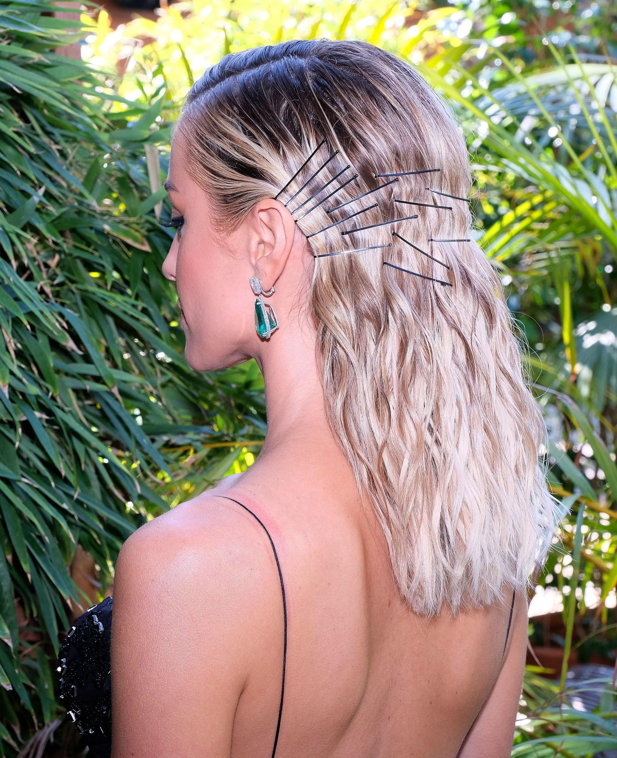 Femme aux cheveux blonds ondulés avec des épingles à cheveux