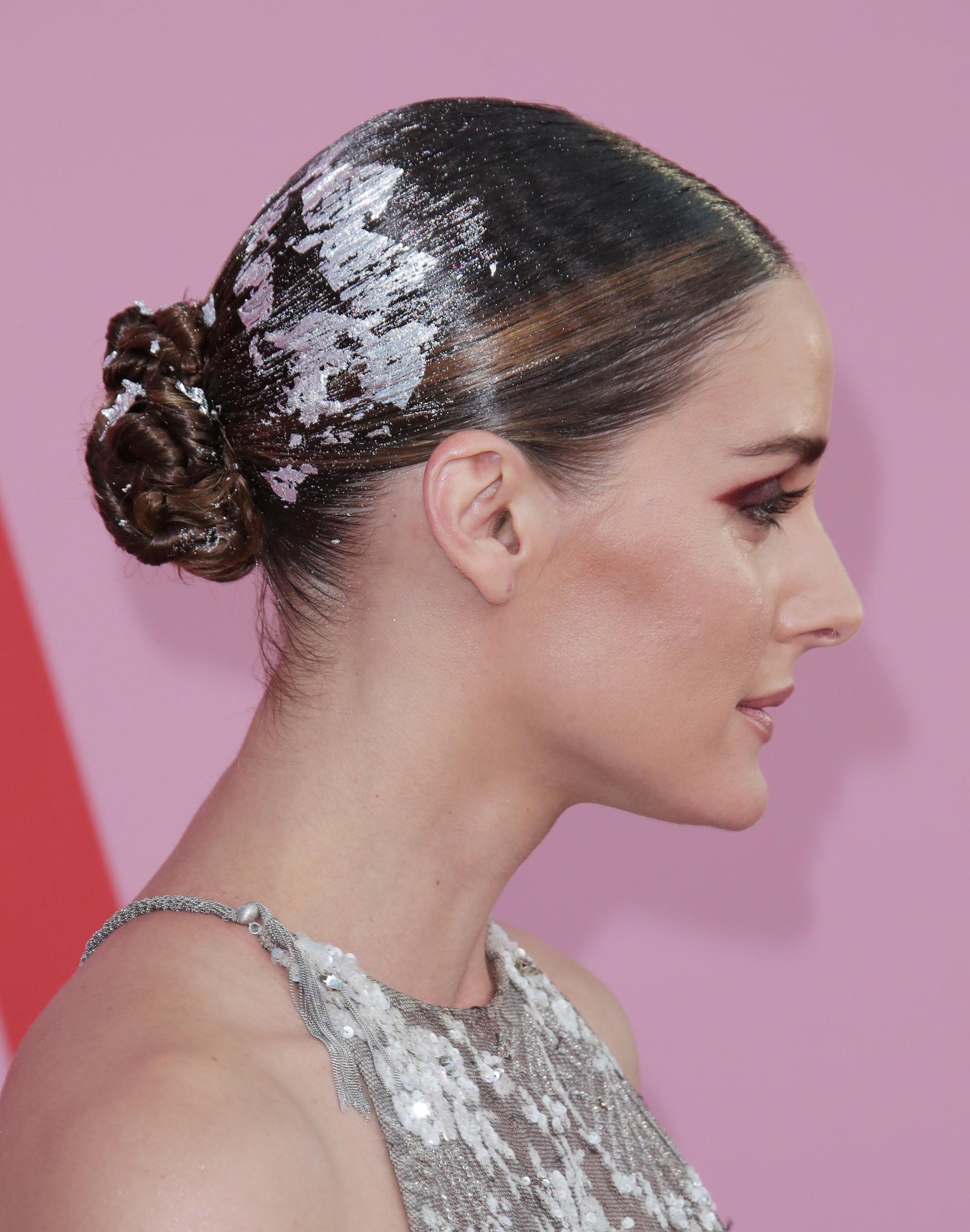 Olivia Palermo avec une coiffure sombre en chignon bas avec des décorations en aluminium