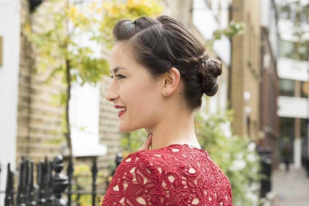 Coiffures de fête : Femme aux cheveux brun foncé coiffée d'un chignon tressé et portant un haut en dentelle noire.