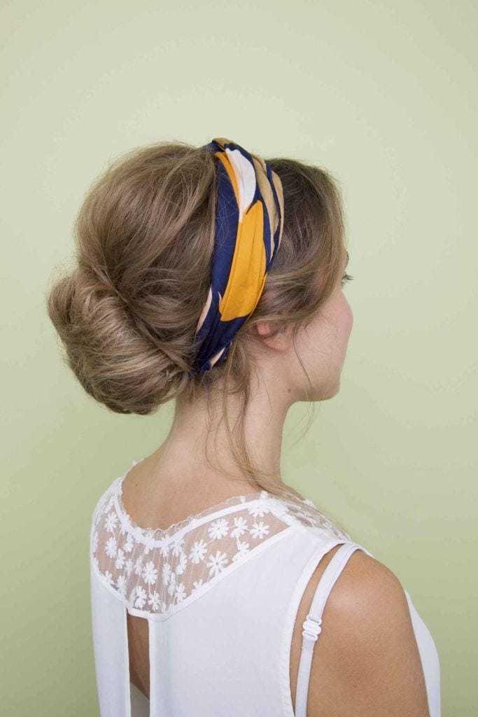 Coiffures de fête : Femme aux cheveux raides blonds foncés, en chignon bas, avec un foulard bleu et jaune, portant un haut blanc.
