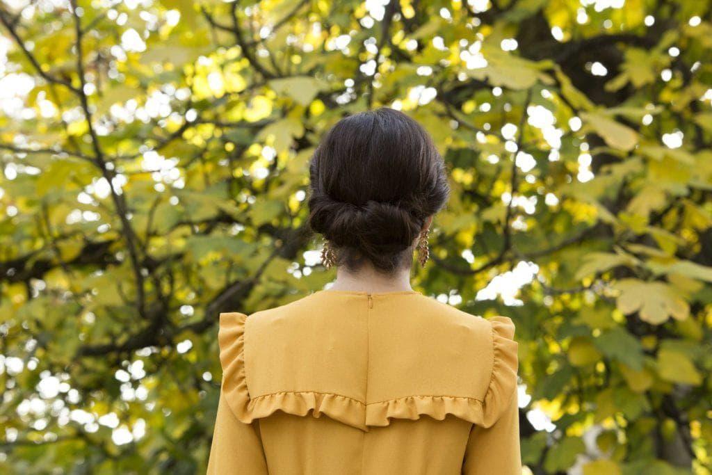 Coiffures de fête : Femme aux cheveux brun foncé en gibson tuck updo portant une robe à volants jaunes.
