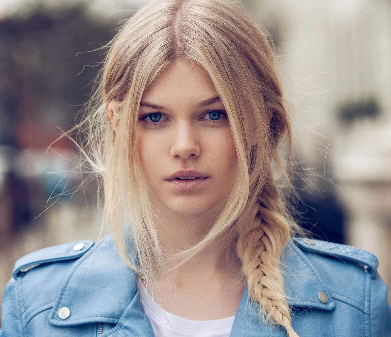 Coiffures de fête : Femme aux cheveux raides blond clair en tresse latérale portant une veste en cuir bleu clair.