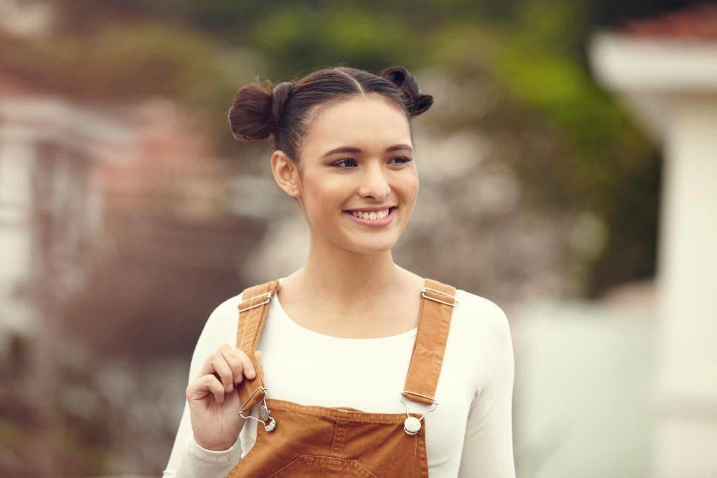 Coiffures de fête : Femme aux cheveux bruns et raides, coiffée en chignon de l'espace, portant une salopette.
