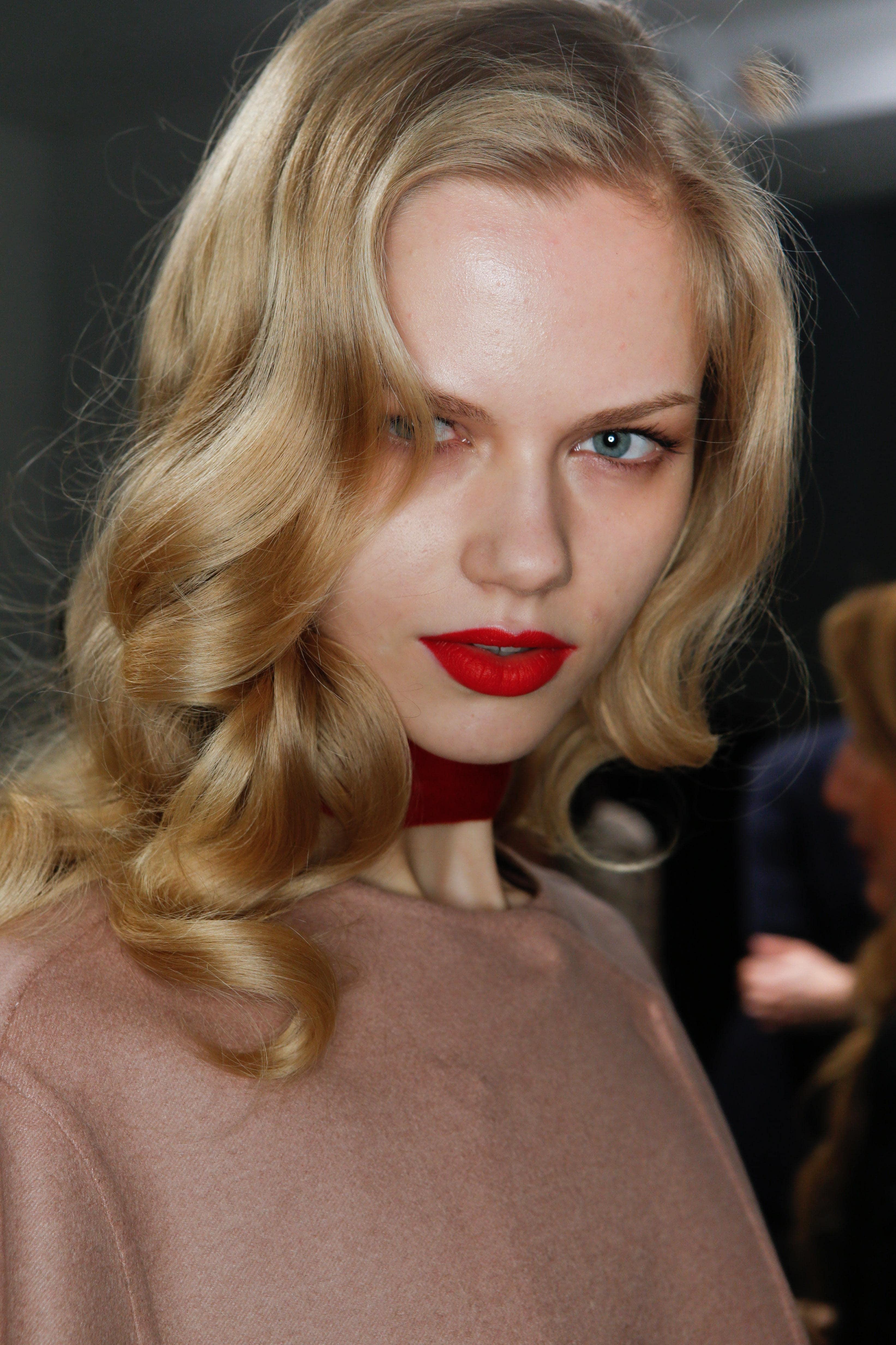 Coiffures de fête : Femme aux cheveux blonds bouclés vintage de longueur moyenne, portant un haut rose doux et un rouge à lèvres rouge vif.