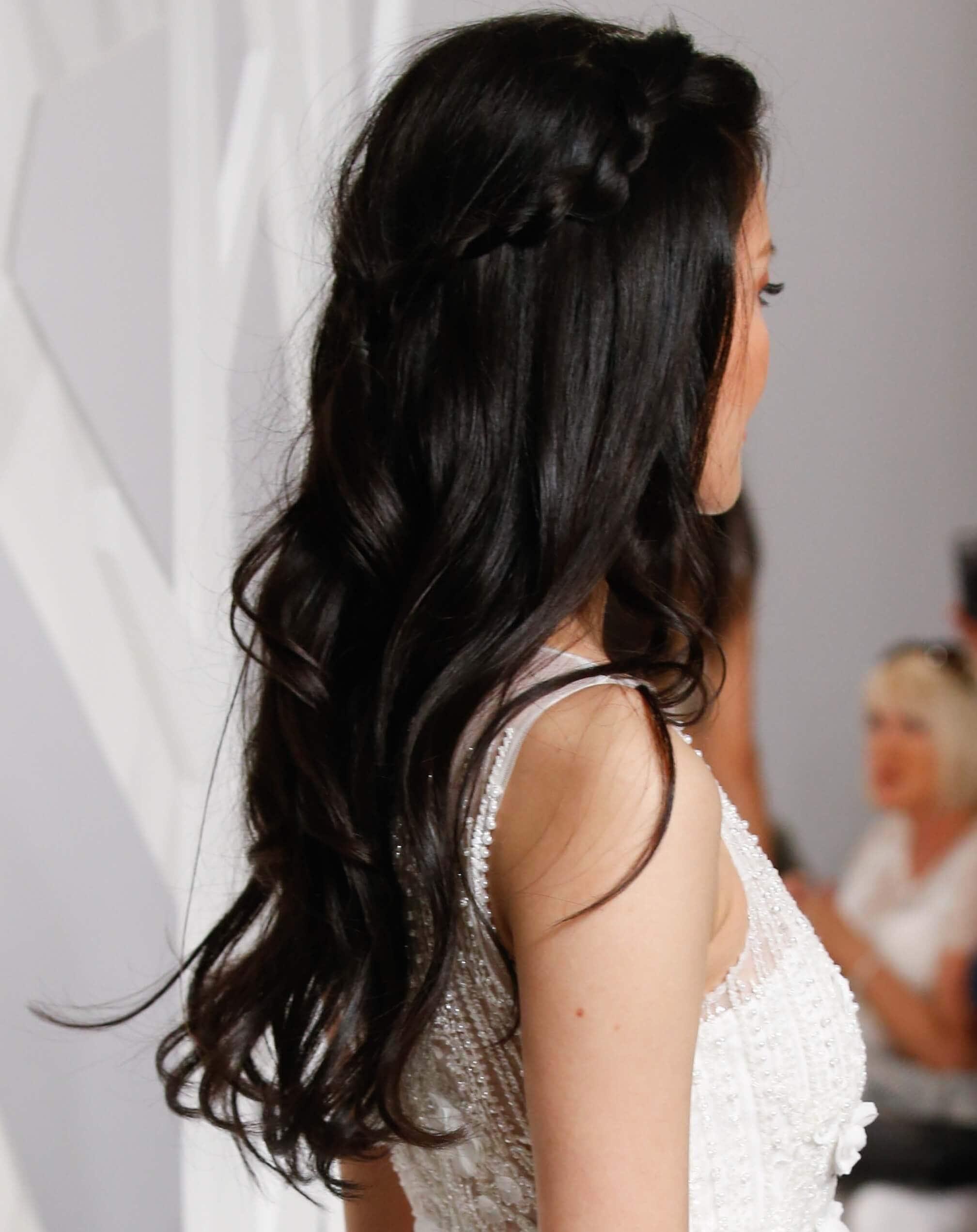 Coiffures de fête : Femme aux longs cheveux bruns ondulés, en style mi-haute, mi-dessous avec des tresses d'accent, portant une robe blanche.