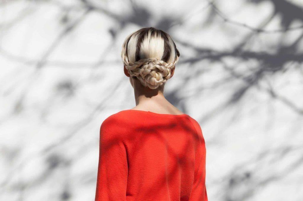 Coiffures de fête : Femme aux cheveux blonds décolorés, coiffée d'un chignon en tresse de serpent et portant un haut rouge.
