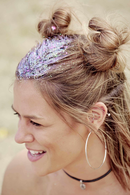 Une femme avec des paillettes dans les cheveux et des petits pains de l'espace