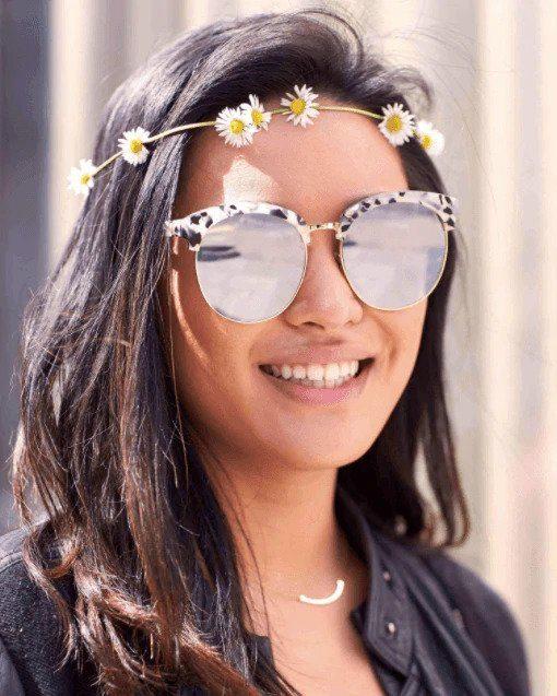 Coiffures de fête : Femme aux cheveux bruns et raides avec une guirlande de tournesol, portant des lunettes de soleil réfléchissantes.