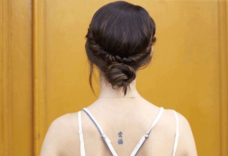Coiffures de fête : Femme aux cheveux bruns raides coiffée en chignon bas torsadé, debout contre un mur jaune.