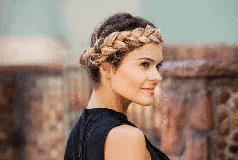 Coiffures de fête : Femme aux cheveux longs blonds en tresse halo, portant un gilet noir.